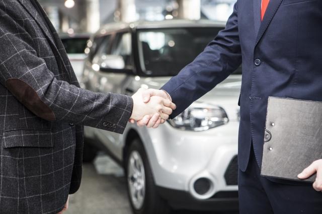 車のディーラーと握手する人