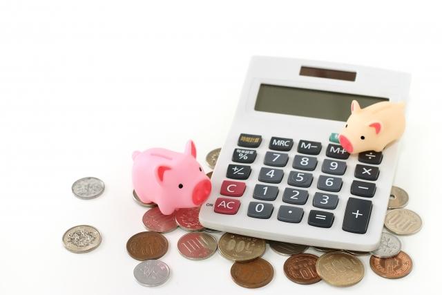 電卓と豚とお金の写真